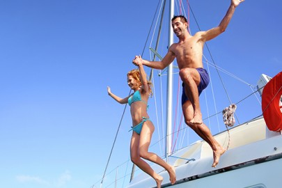 couple-jumping-off-sailboat-in-caribbean