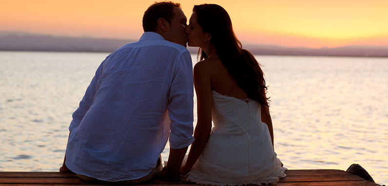romantic-couple-kissing-on-the-beach-at-sunset