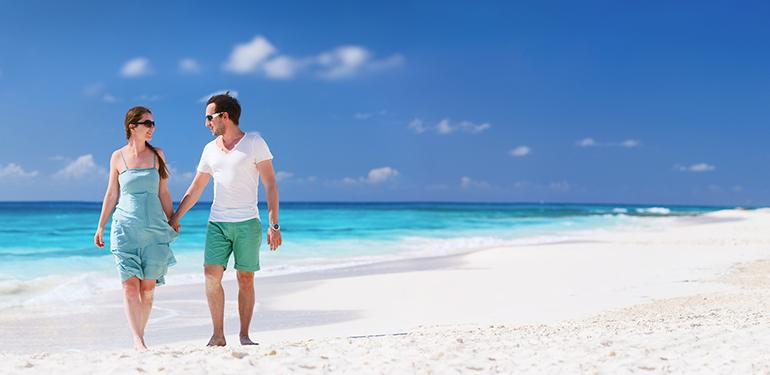couple-walking-on-caribbean-beach